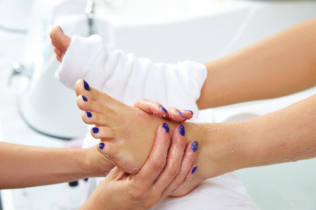 pedicure: foot scrub pedicure woman leg in nail salon on chair sofa
