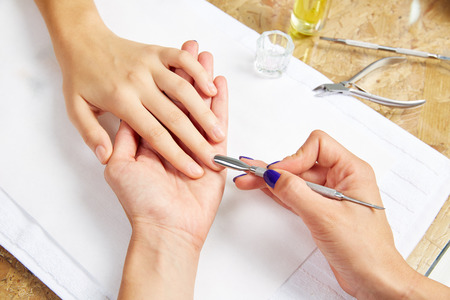 cuticle pusher: Cuticle pusher tool in nails salon woman hands treatment Stock Photo