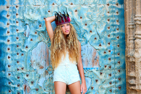 hair feathers: Blond teen girl tourist in Mediterranean old town door with colorful feathers on hair Stock Photo