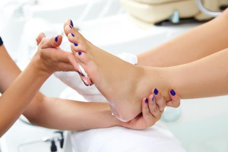 manicure set: Pedicure moisturizing cram after dead skin remover foot rasp woman in nail salon Stock Photo
