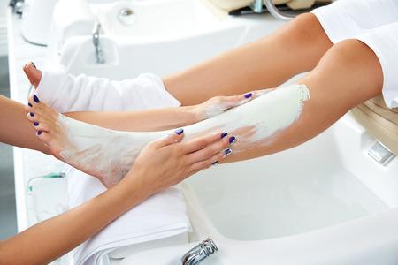 pedicura: Pedicura aplying m�scara hidratante nutritiva en las piernas de la mujer en sal�n de u�as