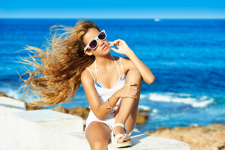 costa blanca: Blond kid teen girl on the beach long with curly hair waving at wind
