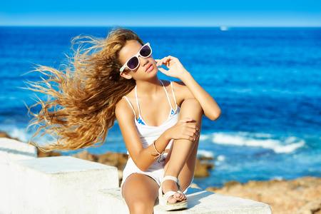 niñas bonitas: Muchacha adolescente rubia niño en la playa con el pelo rizado largo ondeando en el viento Foto de archivo