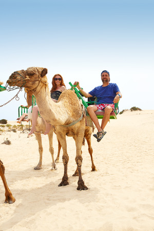 Couple riding Camel in Fuerteventura desert at Canary Islands of Spain photo