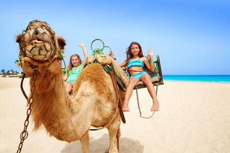 desert island: Girls riding Camel in Fuerteventura desert at Canary Islands of Spain
