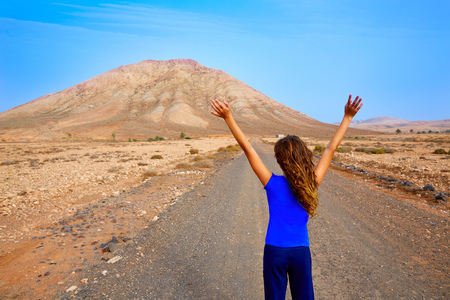 stone volcanic stones: Fuerteventura girl in Tindaya mountain at Canary Islands of Spain