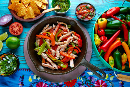 piquancy: chicken fajitas in a pan with sauces chili and sides Mexican food Stock Photo