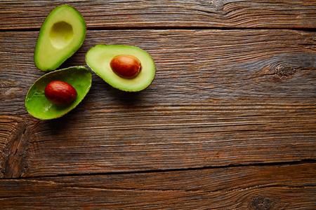 albero da frutto: avocado tagliato a bordo di tabella di legno invecchiata tagliato a metà