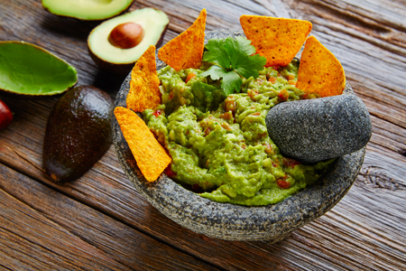 nachos: Guacamole with nachos avocado in Mexican molcajete in aged wood table
