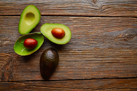 cutted: avocado cut on aged wood table board cutted half
