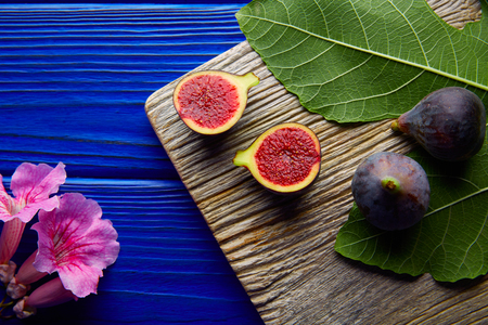 cutted: figs raw cutted fruits and fig tree leaves on blue wooden table