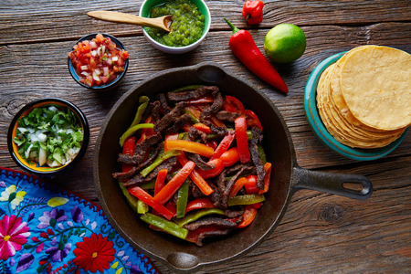 piquancy: Beef fajitas in a pan with sauces chili and sides Mexican food Stock Photo