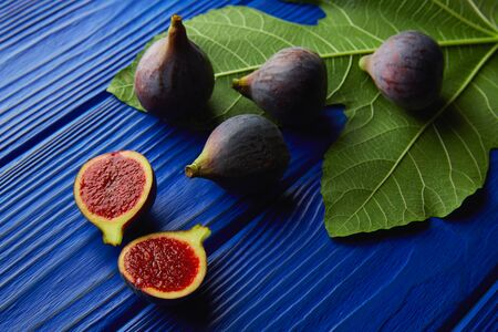 fig leaf: figs raw cutted fruits and fig tree leaves on blue wooden table