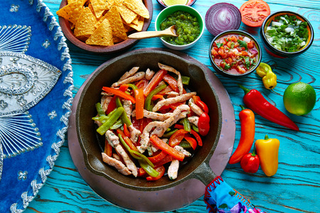 chicken fajitas in a pan with sauces chili and sides Mexican food Stok Fotoğraf