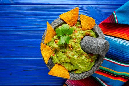 Guacamole con nachos de aguacate en molcajete mexicana en mesa de madera azul