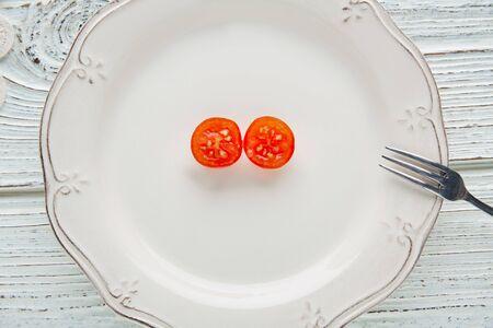 tomate cherry: tomate cereza corte abierto en la placa blanca concepto minimalista de comida vegetariana cruda Foto de archivo