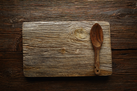 wood board: Aged wood cutting board copyspace background with olive tree wood spoon Stock Photo