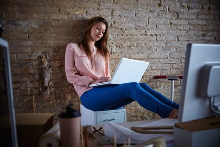 casual office: Businesswoman casual sitting at office working with laptop computer feet on table relaxed Stock Photo