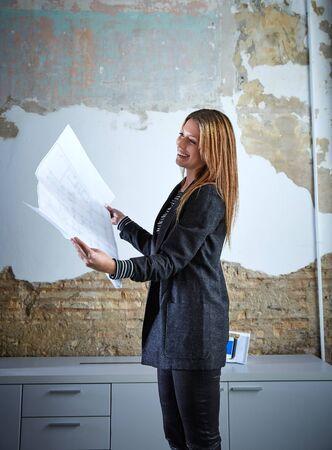 woman working: Architect woman working holding plan paper at office