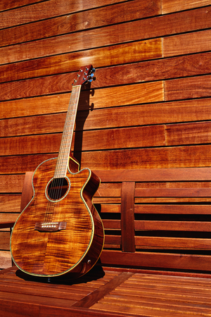 monochromatic: acoustic brown guitar in a wooden stripes wooden wall monochromatic Stock Photo