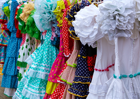 traditional goods: gypsy dresses hanging in a row in an andalusian Spain outdoor market