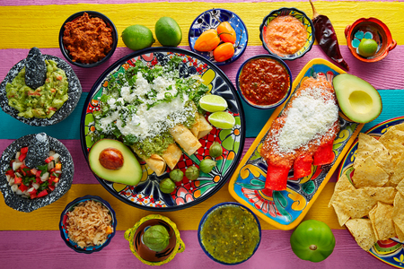 Green and red enchiladas with mexican sauces mix in colorful table Stock Photo