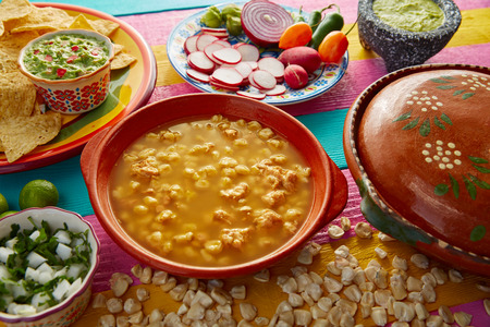 mote: Green Pozole verde with blanco mote corn and ingredients on colorful table Stock Photo