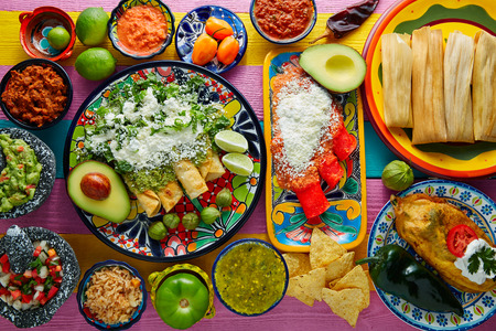 Green and red enchiladas with mexican sauces mix in colorful table