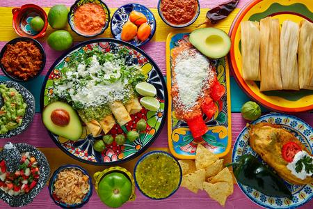 Groene en rode enchiladas met Mexicaanse sauzen mix in kleurrijke tafel