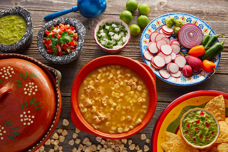blanco: Green Pozole verde with blanco mote corn and ingredients on wooden table