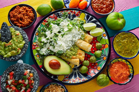 plato de comida: enchiladas verdes comida mexicana con guacamole y salsas en la mesa colorido Foto de archivo