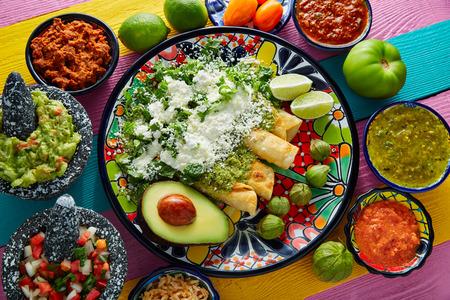 Green enchiladas Mexicaans eten met guacamole en sauzen op kleurrijke tafel