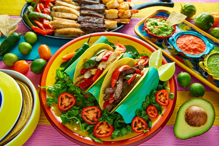 Mexican chicken and beef fajitas tacos in colorful table with sauce Stock Photo