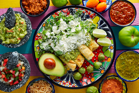 Green enchiladas Mexican food with guacamole and sauces on colorful table