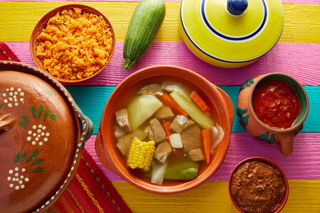 res: Caldo de res Mexican beef broth in table with sauces
