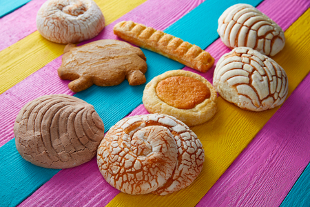 Mexican pastries concha puerquito ojo buey in a colorful wood background Stock Photo