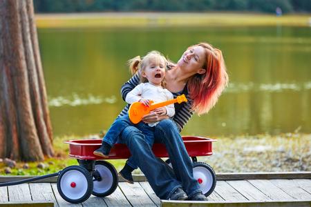 pull toy: madre e hija que juega el juguete de la guitarra que canta en el lago del parque con el carro de arrastre