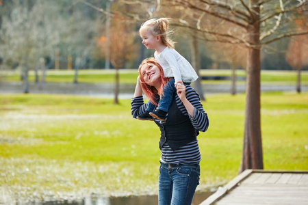 boroughs: Mother holding daughter sit in her shoulders at the park lake Stock Photo