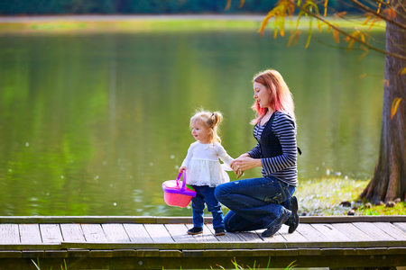 boroughs: Kid girl and mother with basket playing in the park lake Stock Photo