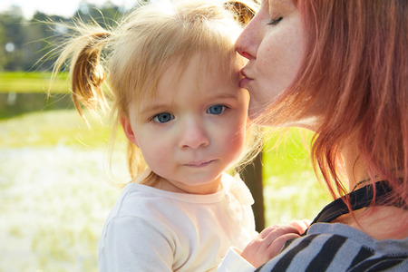 boroughs: Mother and daughter portrait hug kissing in a park outdoor Stock Photo
