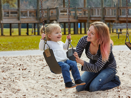 young woman smiling: Mother and daughter in a swing having fun at the park playground Stock Photo