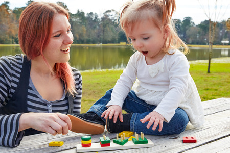 boroughs: Mother and daughter playing with color shapes game in a park lake