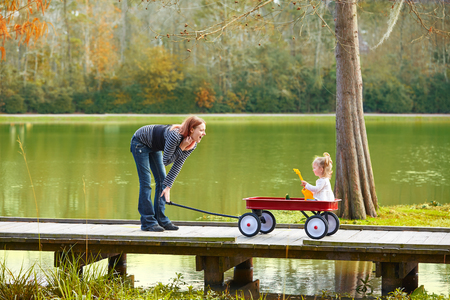 boroughs: Kid girl and mother walking in the park lake with pull cart