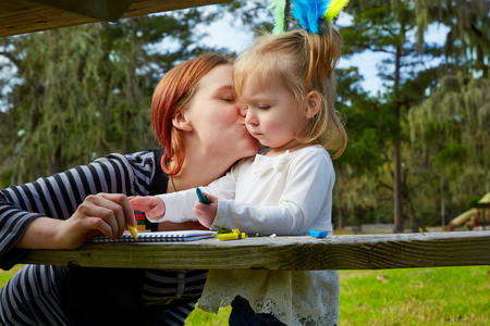 mother kissing daughter: Mother kissing daughter drawing colors in a park lake Stock Photo