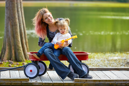 pull toy: mother and daughter playing toy guitar in the park lake with pull cart