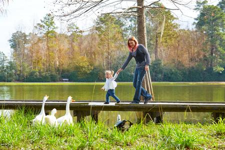 animales del bosque: muchacha niño y la madre juega con los patos en el lago del parque