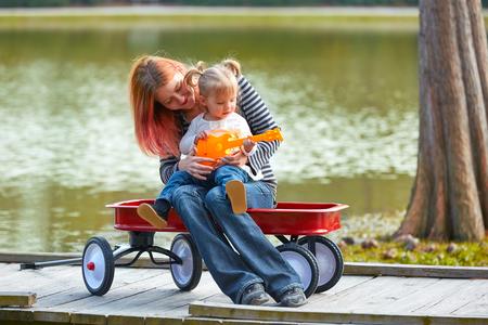 pull toy: madre e hija a tocar la guitarra de juguete en el lago del parque con el carro de arrastre
