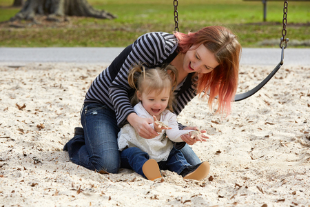 boroughs: Mother and daughter playing with sand having fun at the park playground