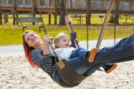 boroughs: Mother and daughter in a swing having fun at the park playground Stock Photo