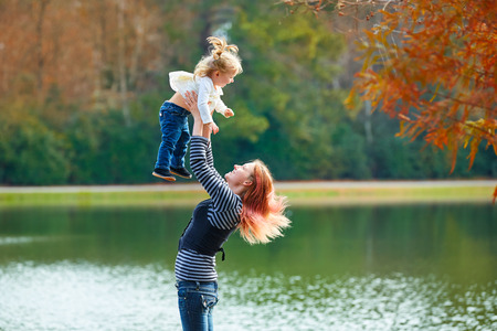 boroughs: Mother playing throwing up baby girl daughter in the park lake